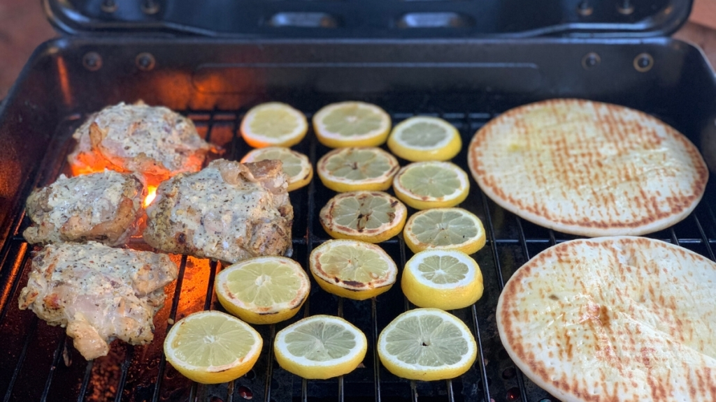 Chicken, lemon slices, and pita bread on grill