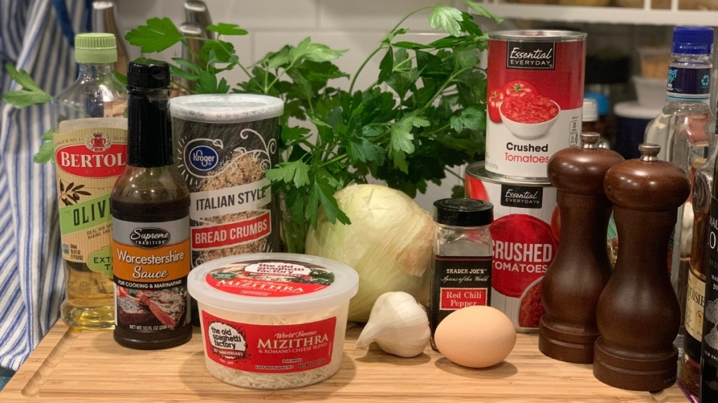 Ingredients for meatballs and sauce, an egg, an onion, eight cloves of garlic, Italian bread crumbs, crushed red pepper flakes, flat-leaf parsley, dried oregano, Worcestershire sauce, two cans crushed tomatoes, salt, pepper, and mizithra cheese.